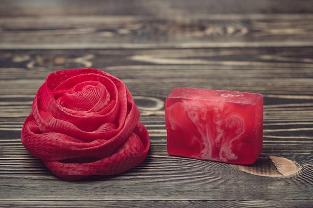 Esponja líquida do banho e cor vermelha de sabão no fundo de madeira
