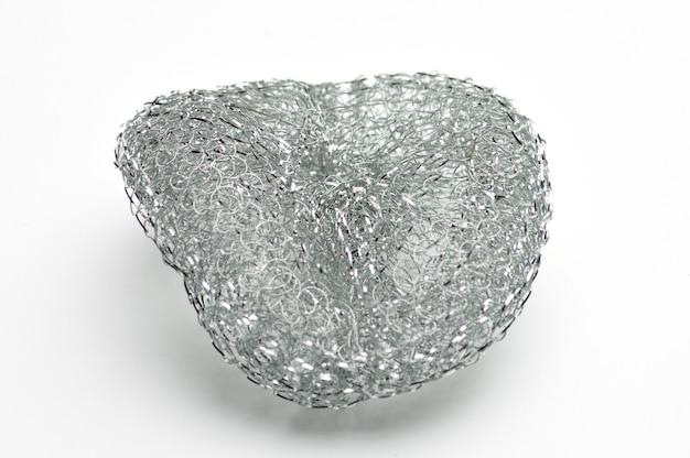 Esponja metálica para lavar pratos e encanamentos em superfície branca isolada