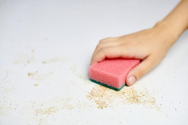 Esponja na mão de uma mulher, removendo a sujeira