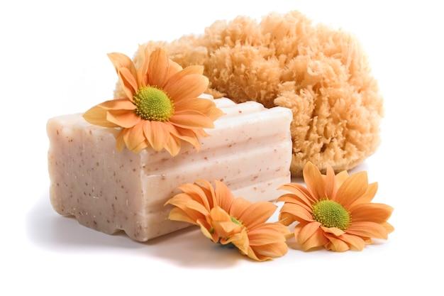 Esponja natural, sabão e flores sobre fundo branco