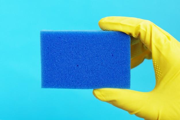 Esponja para lavar a louça na mão em uma luva de borracha amarela