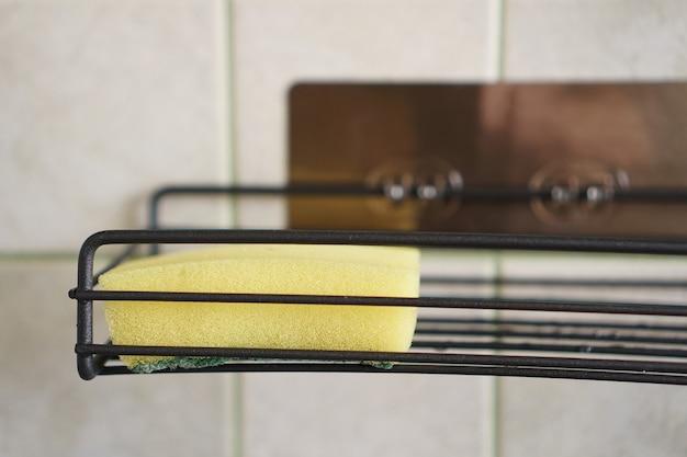 Esponja para lavar pratos na prateleira de metal da cozinha. conceito de limpeza. close-up interior. ninguém.