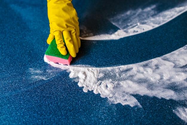 Esponjas coloridas para a limpeza em um fundo azul e mãos amarelas nas luvas.
