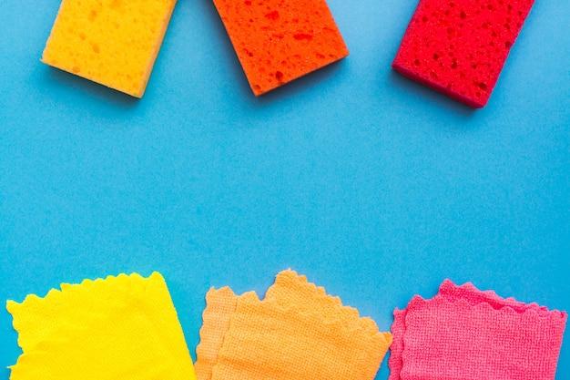Esponjas coloridas para lavar pratos e panos de microfibra ficam nas fileiras acima e abaixo, sobre um fundo azul. conceito de ferramentas de limpeza. copie o espaço
