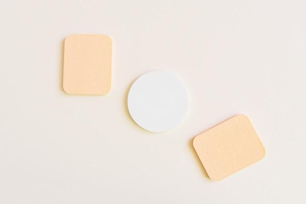 Esponjas cosméticas em uma cor bege. o conceito de cuidados com a pele do rosto e do corpo, cosmetologia. minimalismo, vista superior. copyspace