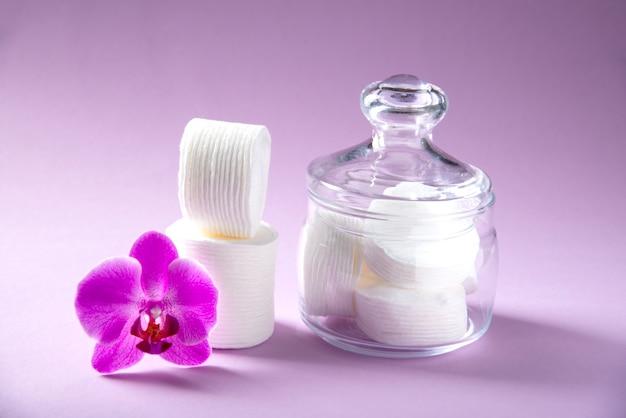 Esponjas de algodão em um frasco de vidro em um fundo rosa com uma flor de orquídea