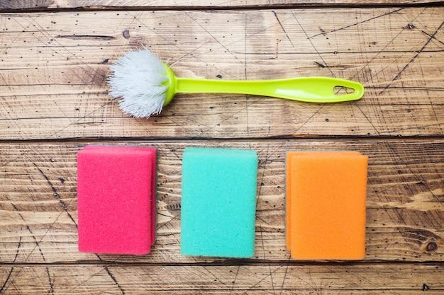 Esponjas e escovas da limpeza no fundo de madeira.