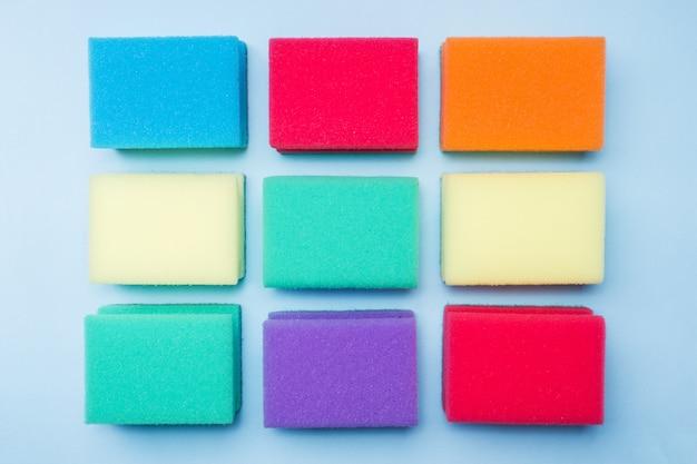 Esponjas e escovas de limpeza das cores no fundo azul.