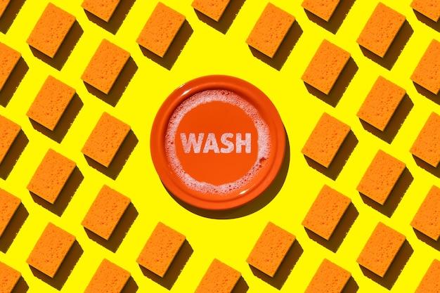 Esponjas laranja de padrão sem emenda para lava-louças e prato laranja com água e espuma