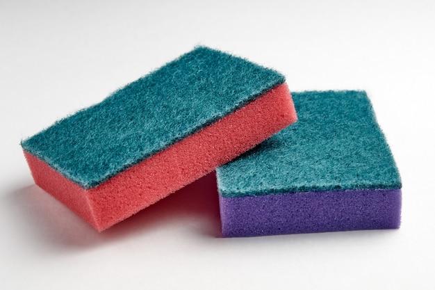 Esponjas multi-coloridas para lavar pratos em um close-up de luz de fundo