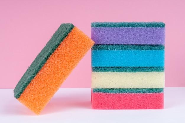 Esponjas multicoloridas para lavar pratos em fundo rosa
