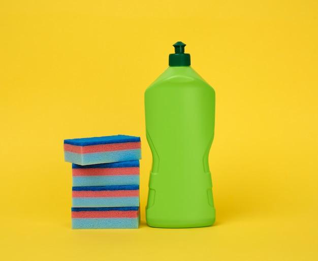 Esponjas retangulares para lavar louça de cozinha azul e garrafa de plástico verde com detergente