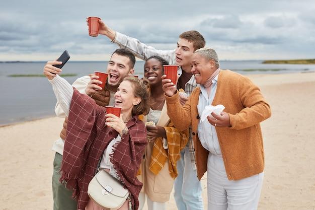 Espontâneo de diversos grupos de amigos tirando uma selfie na praia no outono, copie o espaço