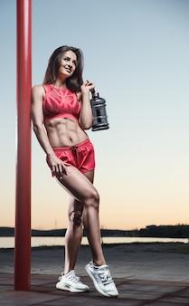 Esporte ao ar livre linda forte sexy atlética muscular jovem caucasiana fitness mulher com garrafa de água bebendo no treinamento