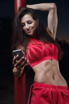 Esporte ao ar livre linda forte sexy atlética muscular jovem caucasiana fitness mulher com treino de telefone celular no ginásio