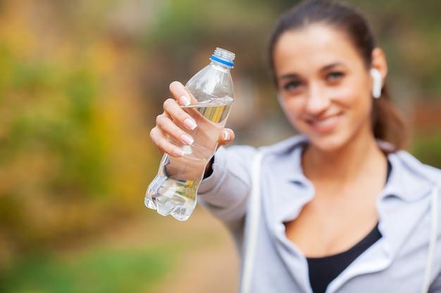 Esporte ao ar livre. mulher bebendo água depois de correr