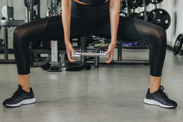 Esporte, aptidão, halterofilismo, halterofilismo e conceito dos povos - próximo acima da mulher que flexiona os braços com peso no gym.