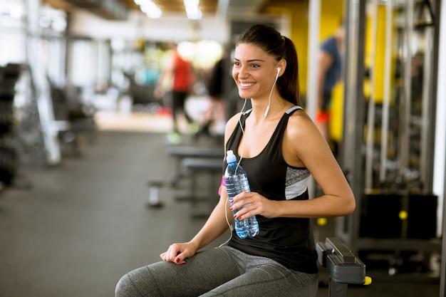 Esporte atraente jovem mulher bebendo água enquanto está sentado e descansando após treino