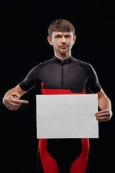 Esporte. ciclista na formação de roupas em fundo preto, segurando a folha de papel em branco. seu texto aqui.