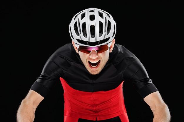 Esporte. ciclista na roupa do treinamento no fundo preto.