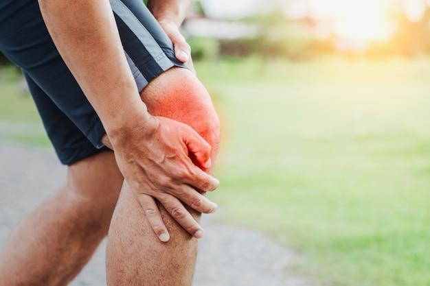 Esporte corredor com lesão no joelho em execução no parque