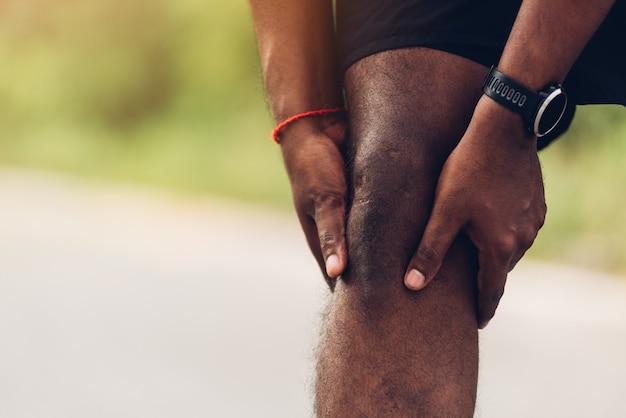 Esporte corredor preto homem desgaste relógio mãos articulação segurar dor no joelho