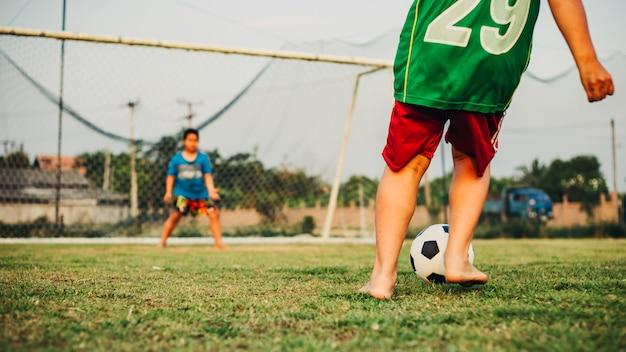 Esporte de ação ao ar livre de um grupo de crianças se divertindo jogando futebol futebol