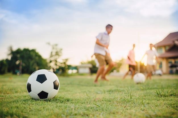 Esporte de ação ao ar livre de um grupo de crianças se divertindo jogando futebol