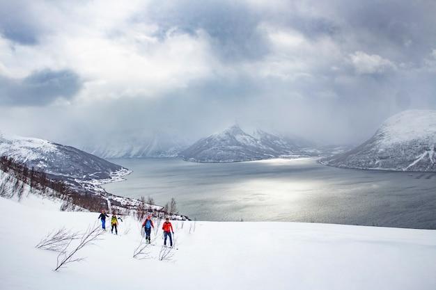 Esporte de inverno, grupo andando na neve, skitouring, fiorde da noruega