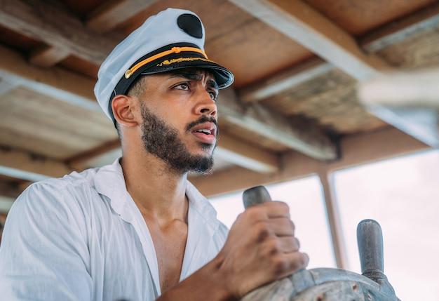 Esporte de vela. capitão encarregado. homem latino-americano com chapéu de capitão de navio