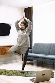 Esporte doméstico para mulheres muçulmanas. menina árabe sorridente em hijab praticando ioga online, assistindo a um tutorial em vídeo no laptop, fazendo exercícios na sala de estar
