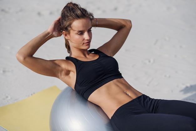 Esporte e conceito de estilo de vida saudável. menina bonita fitness fazendo exercícios de estômago com ajuste bola na praia. jovem mulher fazendo exercícios de pilates.