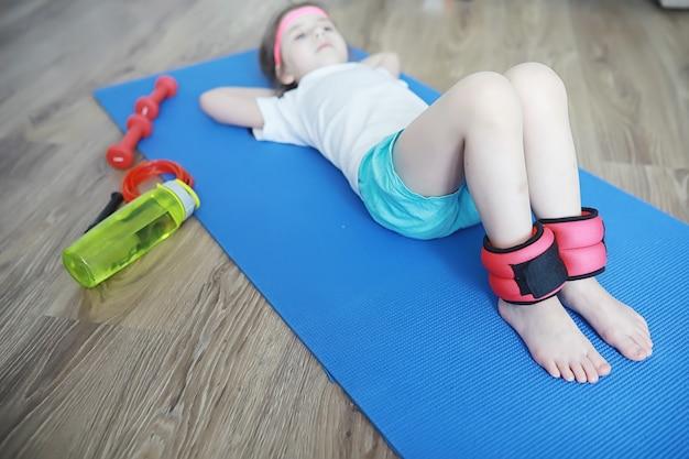 Esporte e estilo de vida saudável. criança praticando esportes em casa. haltere de tapete de ioga e corda de pular. currículo desportivo com conceito de exercícios em casa.