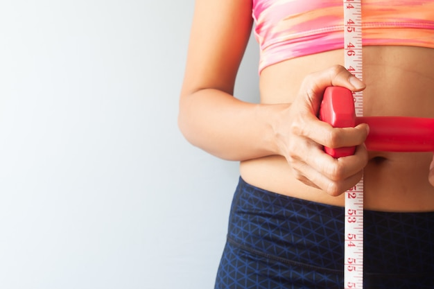 Esporte e mulher saudável segurando halteres com fita métrica no corpo