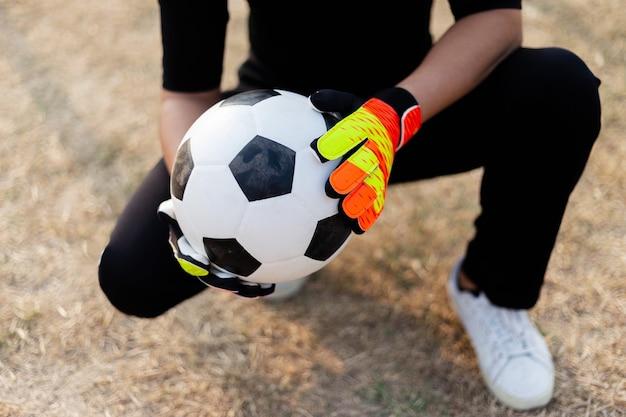 Esporte e recreação conceito um goleiro adolescente do sexo masculino vestindo roupa preta e um par de luvas coloridas segurando uma bola de futebol.