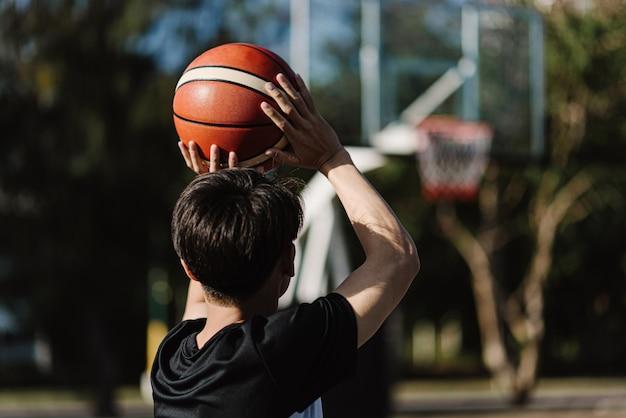 Esporte e recreação conceito um jovem adolescente do sexo masculino praticando tiro de basquete separadamente na quadra depois da escola.