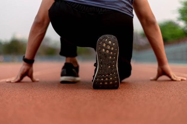 Esporte e recreação conceito um jovem adolescente do sexo masculino vestindo roupa escura em uma posição de preparação antes de começar a correr na pista de corrida.