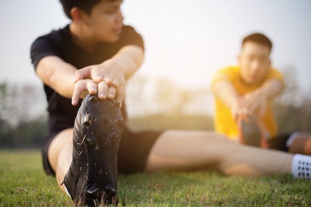 Esporte e recreação conceito um jovem adulto do sexo masculino se preparando antes do treino que ajuda a reduzir as dores musculares e diminuir o risco de lesões.