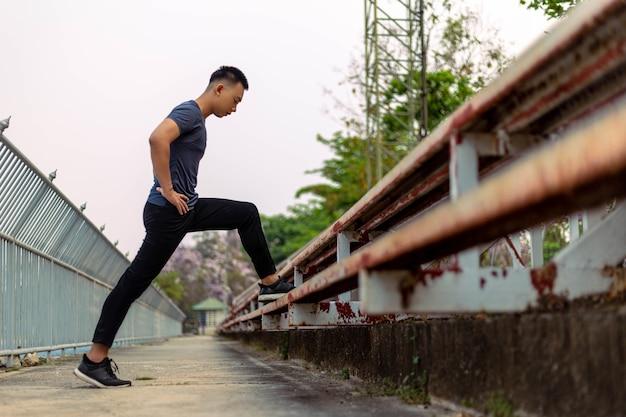 Esporte e recreação conceito um jovem do sexo masculino fazendo aquecimento, alongando cada parte de seu corpo como preparação antes do exercício.