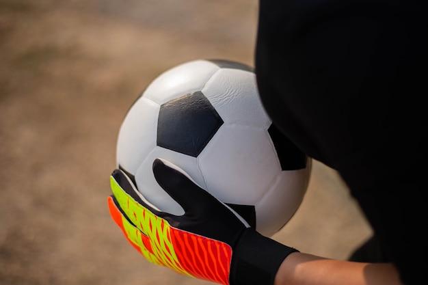 Esporte e recreação conceito um jovem goleiro do sexo masculino usando as duas mãos para pegar a bola para evitar que o time adversário marque.