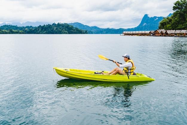 Esporte e recreação. jovem desfrute de caiaque de férias em cheow lan lake, tailândia