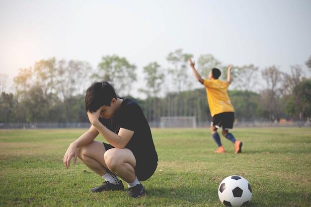 Esporte e recreação um momento de vitória e derrota de dois jogadores após a partida de futebol.