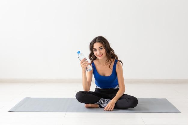Esporte, estilo de vida saudável, conceito de pessoas - jovem bebendo água após o esporte