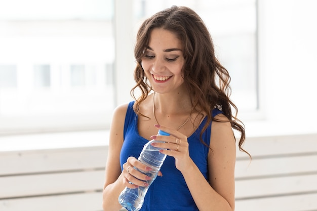 Esporte, estilo de vida saudável, conceito de pessoas. jovem mulher bebendo água depois do esporte.