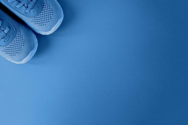 Esporte, estilo de vida saudável, cor do conceito do ano 2020. tênis novos em fundo na cor azul clássico da moda. copie o espaço. para o blog de fitness, mídias sociais. horizontal. estilo minimalista plano lay