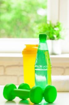 Esporte, estilo de vida saudável e objetos conceito - close up de halteres, garrafa de água