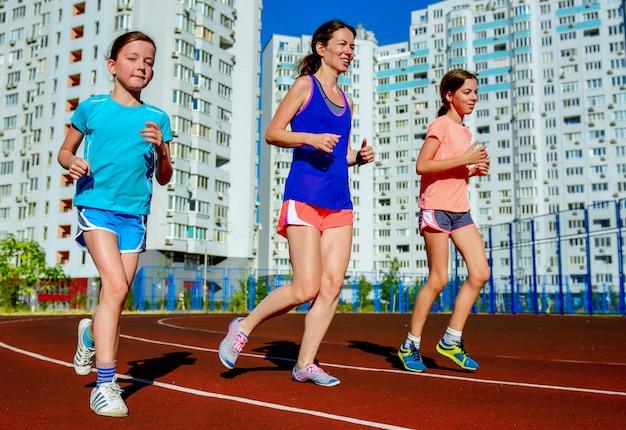 Esporte familiar e fitness, mãe feliz e crianças correndo na pista do estádio ao ar livre, conceito de estilo de vida ativo saudável de crianças