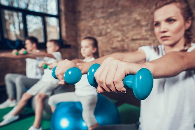 Esporte familiar trabalho com halteres em bolas de fitness
