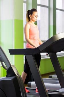 Esporte, fitness, estilo de vida, tecnologia e conceito dos povos - mulher de sorriso que exercita na escada rolante no gym