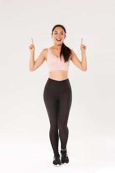 Esporte, ginástica e conceito de corpo saudável. comprimento total da alegre sorridente menina asiática fitness, atleta feminina em roupas esportivas, mostrando o anúncio, apontando o dedo para cima e convidando para o treino, treino.